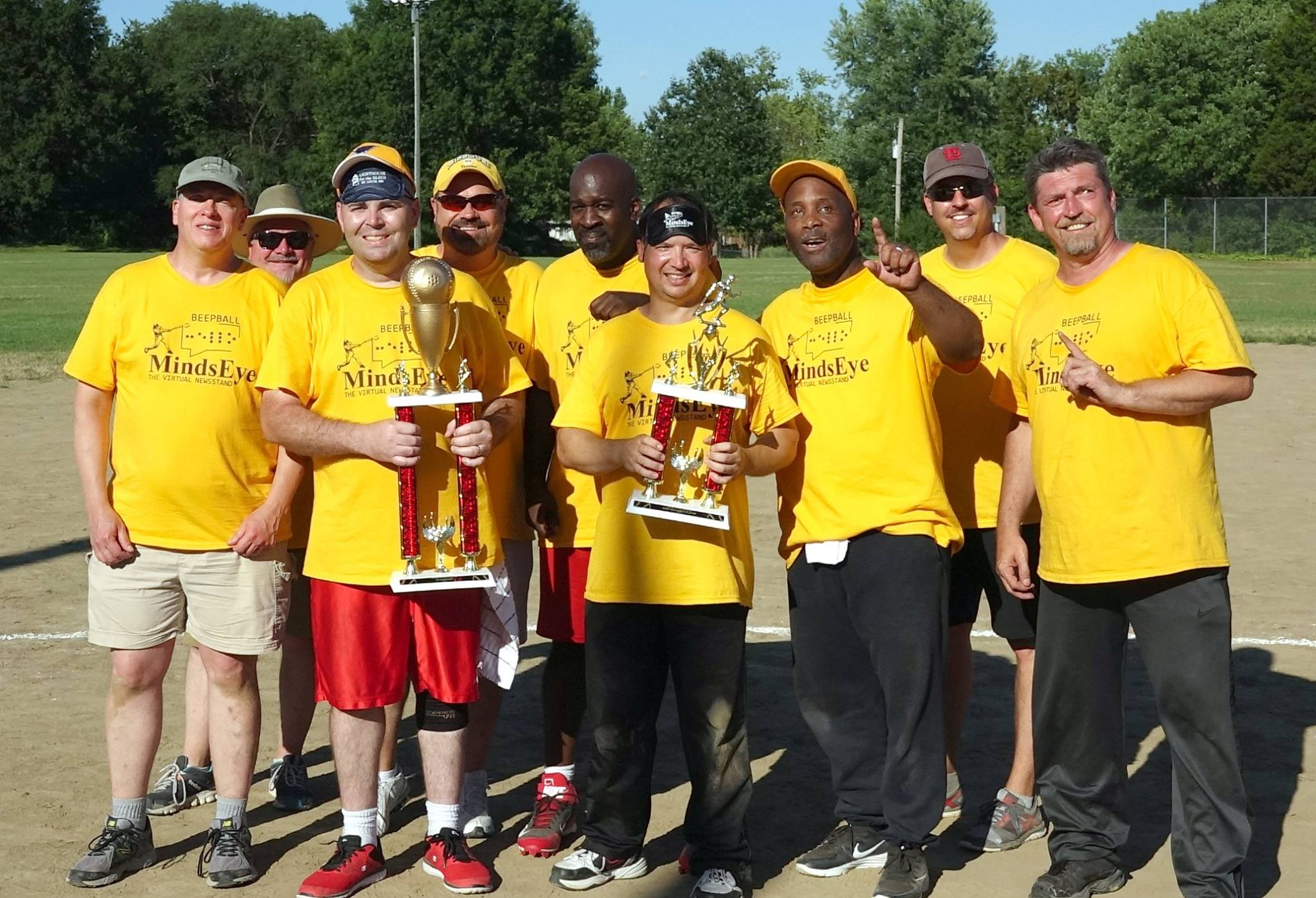 2017 Beepball Champs Lighthouse for the Blind Saint Louis stand together on the baseball field wearing bright yellow MindsEye Beepball T-shirts holding large trophies